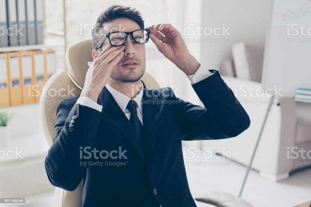 Health care healthcare people. Close up portrait of sad unhappy exhausted frustrated tired sleepy employee manager banker touching eyes holding glasses sitting at light modern office stock photo