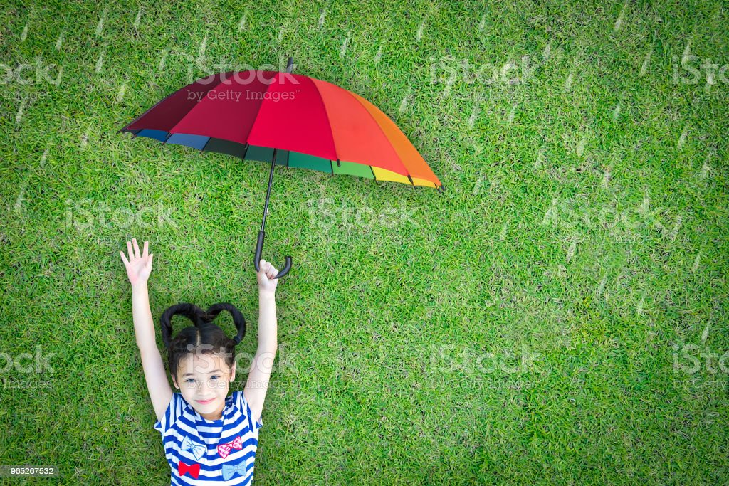 Health care insurance concept for family and children medical healthcare protection, flu prevention immunization with happy asian school girl kid holding umbrella under the rain on green lawn zbiór zdjęć royalty-free