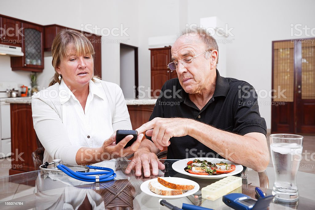 Health care professional and senior diabetic patient stock photo