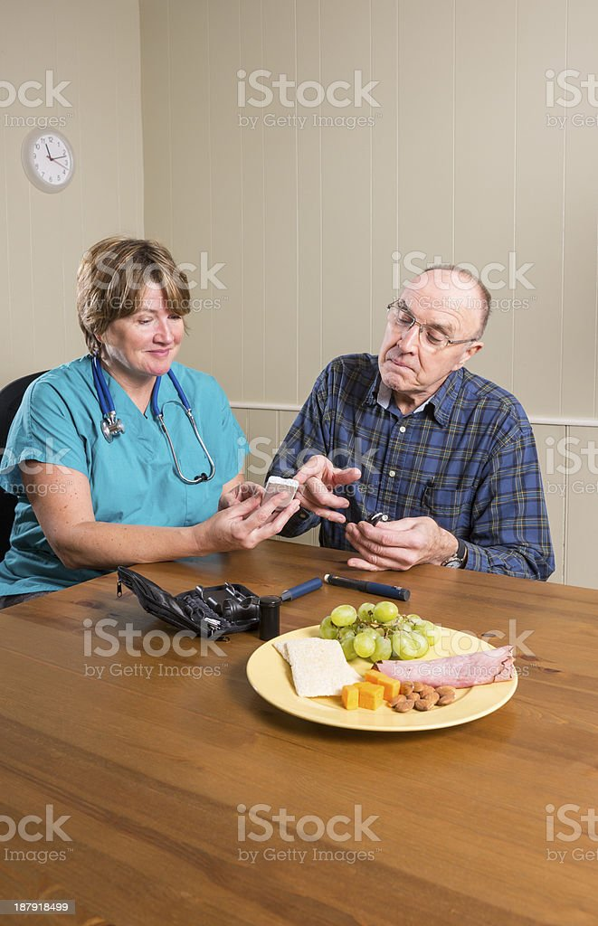 Health care professional helping a diabetic patient royalty-free stock photo