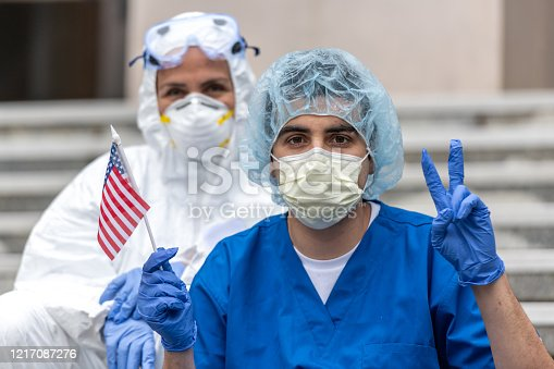 Multi-ethnic Health care worker during a break looking at the camera holding a US flag showing a two fingers victory sign