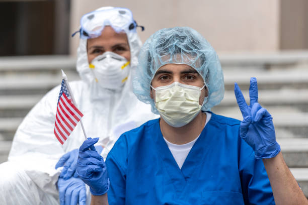 Health care worker during a break looking at the camera holding a US flag showing a two fingers victory sign Multi-ethnic Health care worker during a break looking at the camera holding a US flag showing a two fingers victory sign flatten the curve stock pictures, royalty-free photos & images