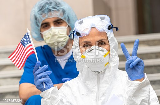 Multi-ethnic Health care workers during a break looking at the camera holding a US flag showing a two fingers victory sign