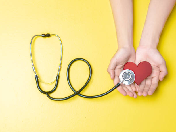 Health day concept Human hands holding red heart and stethoscope over yellow color background. Health day concept world health day stock pictures, royalty-free photos & images