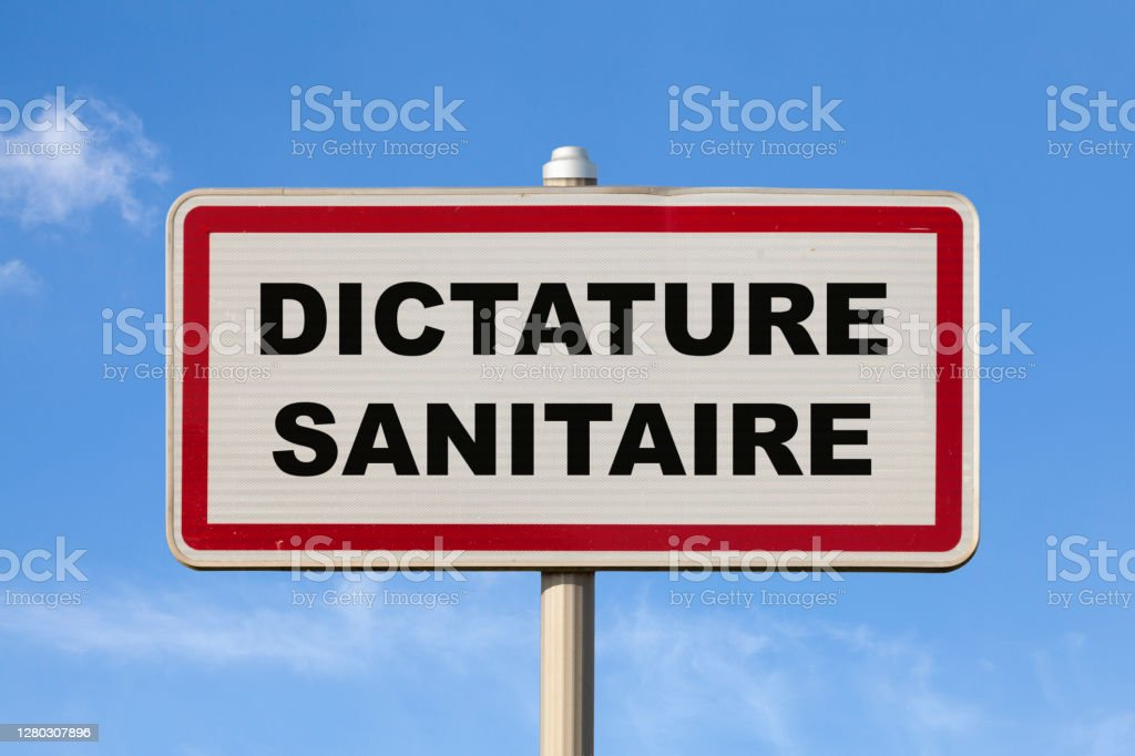 """Health dictatorship - French entry city sign A French entry city sign against a blue sky with written in the middle in French """"Dictature sanitaire"""", meaning in English """"Health dictatorship"""". Authority Stock Photo"""