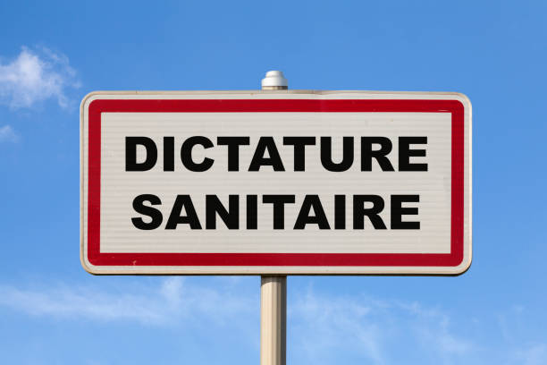 Health dictatorship - French entry city sign stock photo