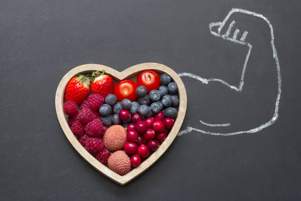 Health diet heart abstract concept with strongman hand on blackboard stock photo