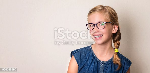 istock Health, education and people concept. Closeup portrait of happy teen girl in braces and eyeglasses. 926268890