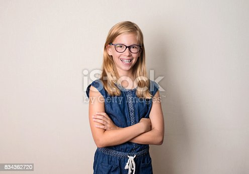 istock Health, education and people concept. Happy teen girl in braces and eyeglasses isolated. 834362720