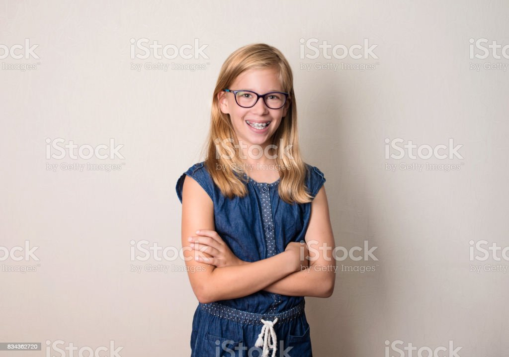Health, education and people concept. Happy teen girl in braces and eyeglasses isolated. stock photo