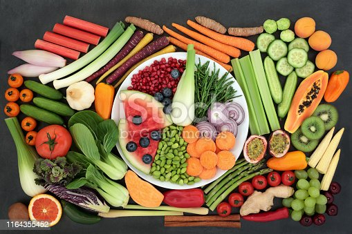 Health food for fitness concept with fresh fruit, vegetables and spices with superfoods very high in antioxidants, complex carbohydrates, anthocyanins, vitamins and dietary fibre. Top view on slate background.