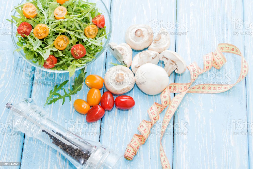 Health food. Fresh mushrooms and arugula salad, cherry tomatoes on light blue background. Diet meals. royalty-free stock photo
