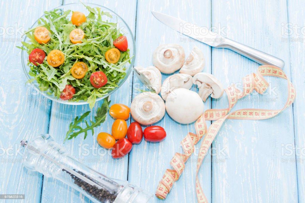 Gesunde Ernährung. Frischen Champignons und Rucola-Salat, Cherry-Tomaten auf Licht blauer Hintergrund. Zum Abnehmen - Lizenzfrei Agrarbetrieb Stock-Foto