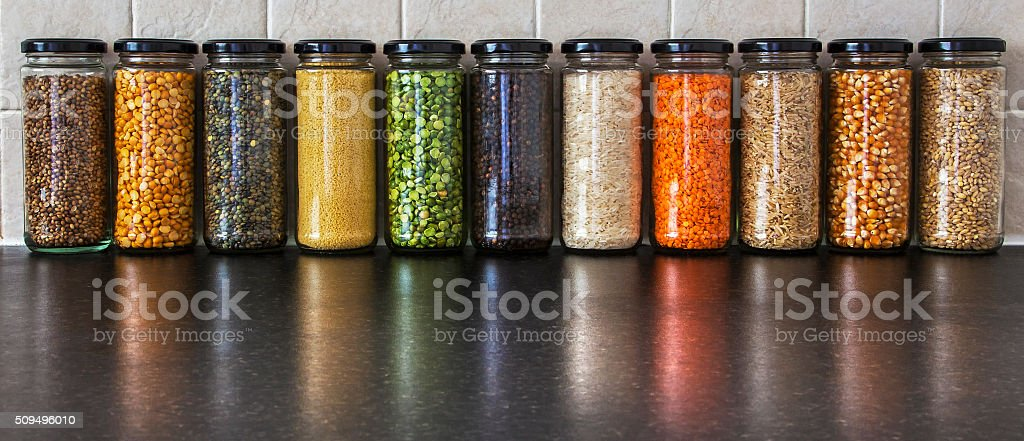 Health Food, variety herbs, seeds and pulses in spice jars. stock photo