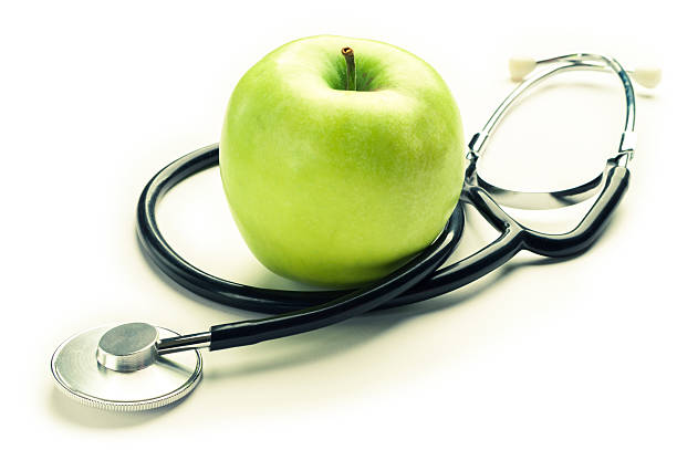 Health. Green apple with medical stethoscope