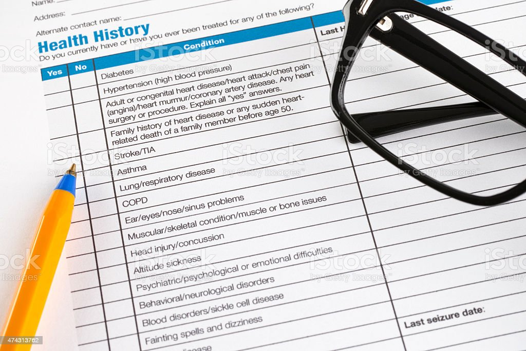 Health History form with glasses and ballpoint pen. stock photo