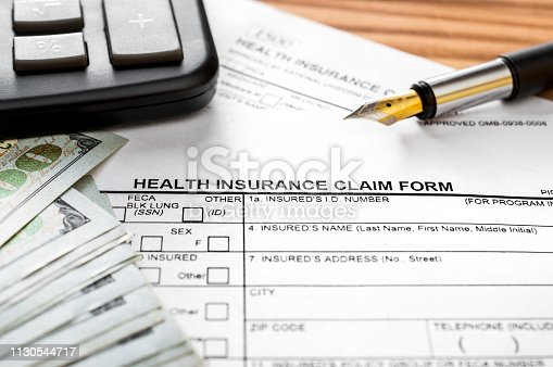 1128824554 istock photo Health insurance claim form with calculator, money and pen on the table. 1130544717