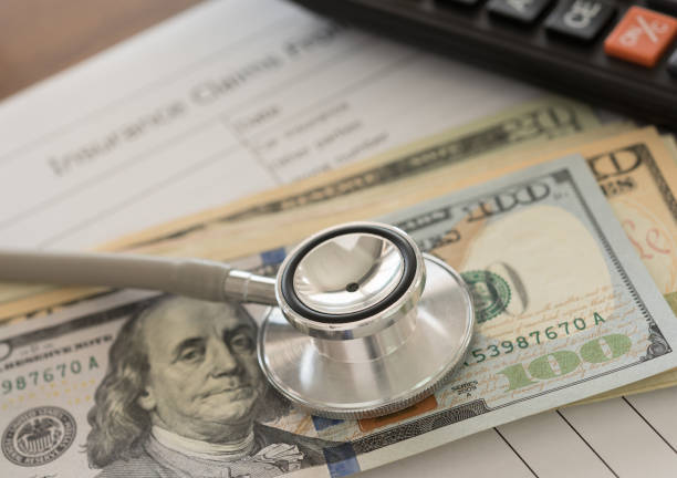 Health insurance claim Health insurance claim concept. Stethoscope on dollar banknote with calculator, health insurance claim form on desk. commercial activity stock pictures, royalty-free photos & images