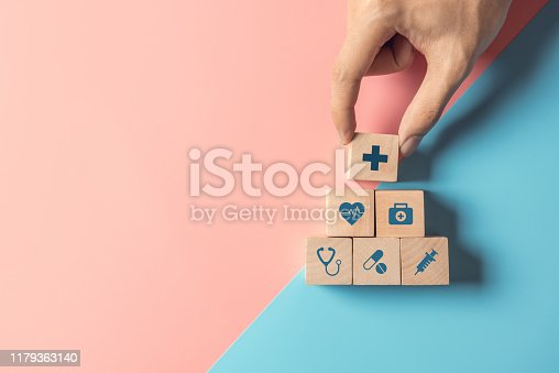 1029077176istockphoto Health Insurance Concept, Hand of man arranging wood cube stacking with icon healthcare medical on pastel blue and pink background. 1179363140