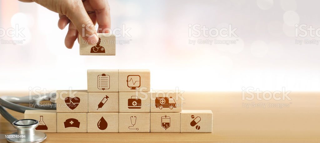 Health Insurance concept, Hand of medicine doctor holding wood block and stacking up icon healthcare medical and stethoscope on backgroud. royalty-free stock photo