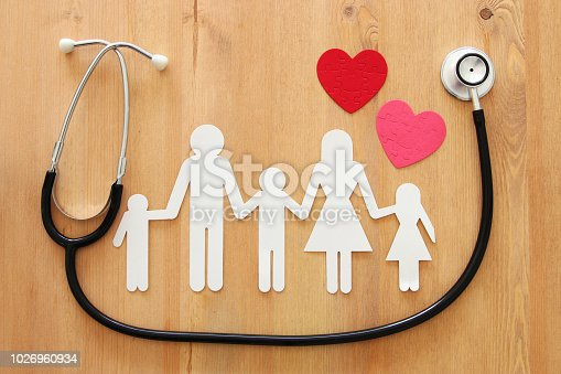 Health Insurance . concept image of Stethoscope and family on wooden table. top view