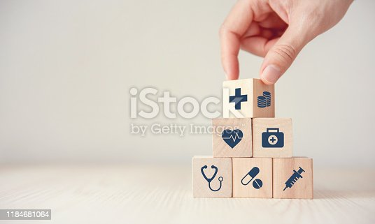 1029077176istockphoto Health Insurance Concept, Reduce Medical Expenses, Hand flip wood cube with icon healthcare medical and coin on wood background, copy space. 1184681064