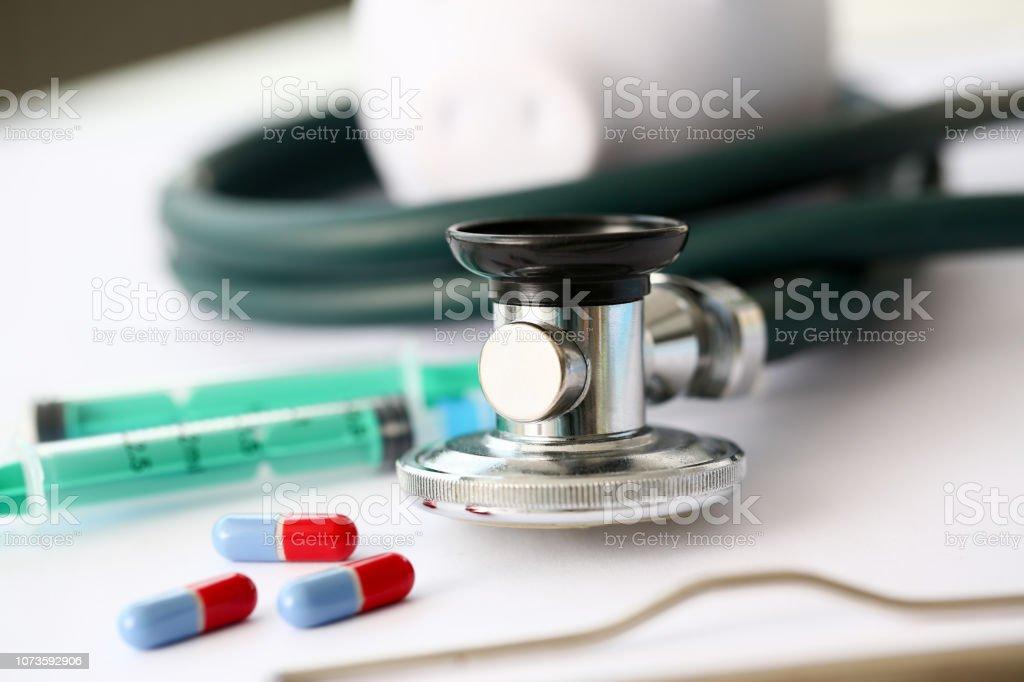 Syringe stethoscope and piggy bank for money on medicine doctor desk...