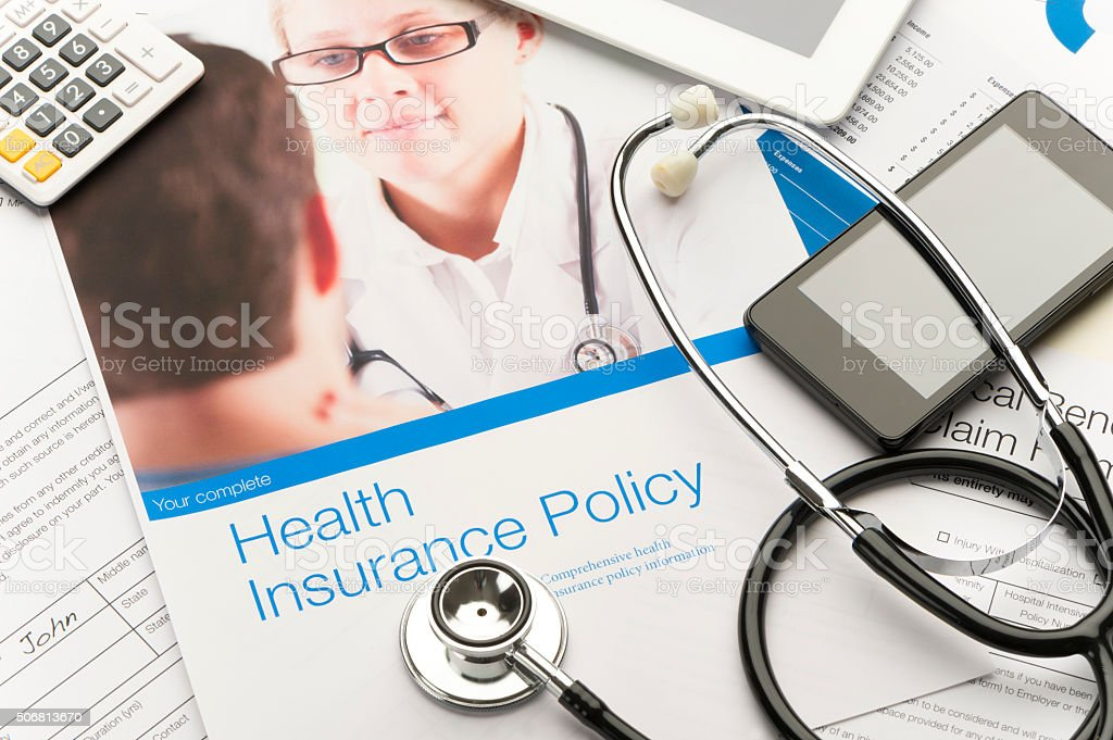 Health Insurance Policy brochure with paperwork. There is also a...