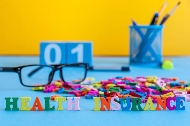Health Insurance - word composed of small colored letters on business workplace of doctor, or insurance agent stock photo