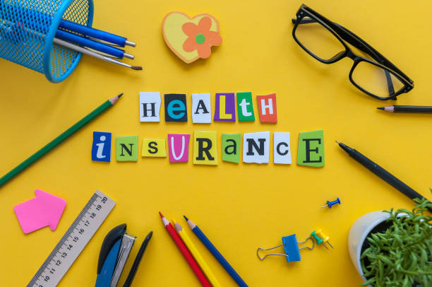 Health Insurance - word of carved letters at office workplace insurance agent stock photo