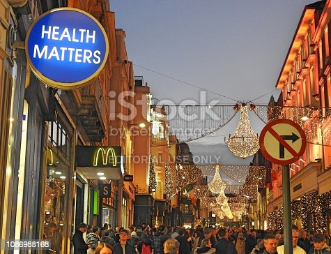 26th December 2018, Dublin, Ireland: A Health Matters sign on a Christmas lights decorated Grafton Street in the evening light, with a McDonald's logo and No Right Turn symbol sign in the background. Theme is healthy eating.