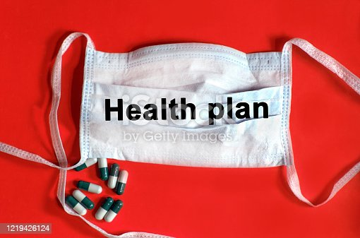 Health plan - text on a protective face mask, tablets on a red background