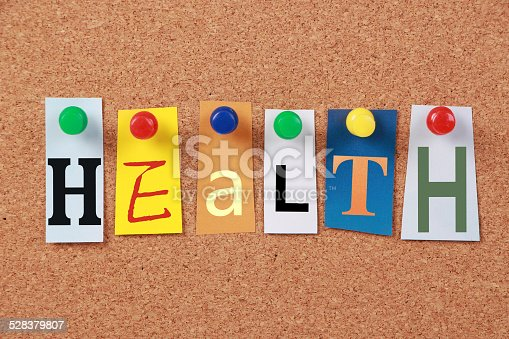 The word Health in cut out magazine letters pinned to a corkboard.