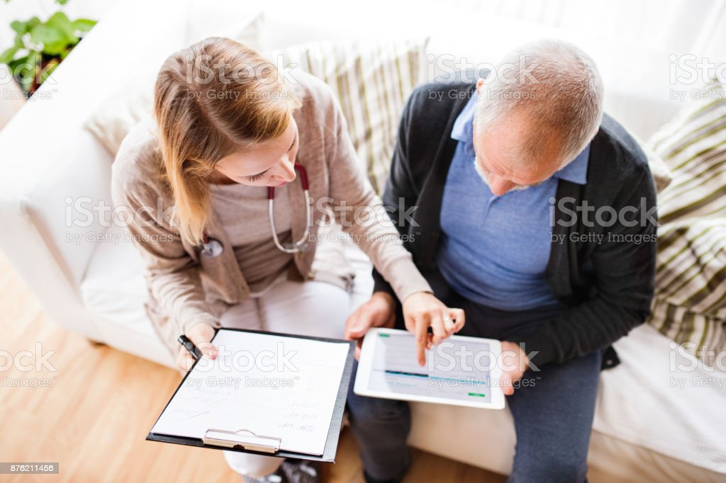Gesundheit-Besucher und ein senior Mann mit Tablet beim Hausbesuch. - Lizenzfrei Alt Stock-Foto