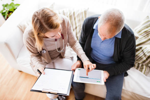 Health visitor and a senior man with tablet during home visit. stock photo