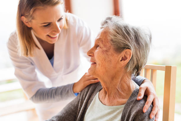 hälsa besökare och en senior kvinna under hem besök. - omsorg bildbanksfoton och bilder