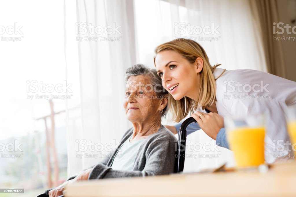 Health visitor and a senior woman during home visit. stock photo