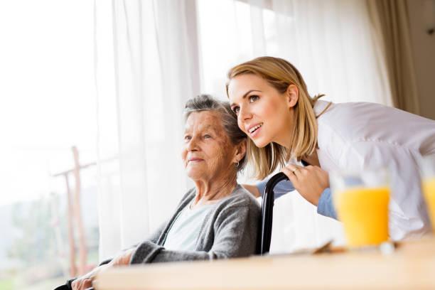 Infirmier et une femme senior au cours de la visite à domicile. - Photo