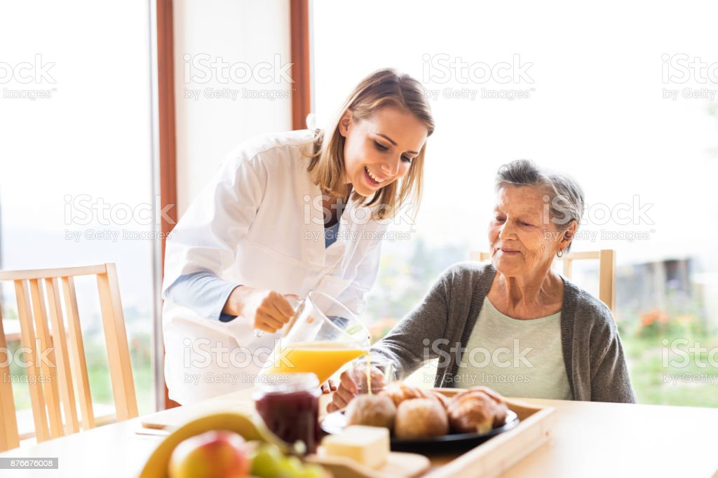 Health visitor and a senior woman during home visit. A nurse pouring...