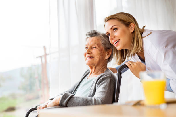 health visitor and a senior woman during home visit. - geriatrics stock pictures, royalty-free photos & images