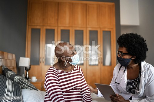 Health visitor and a senior woman during nursing home visit