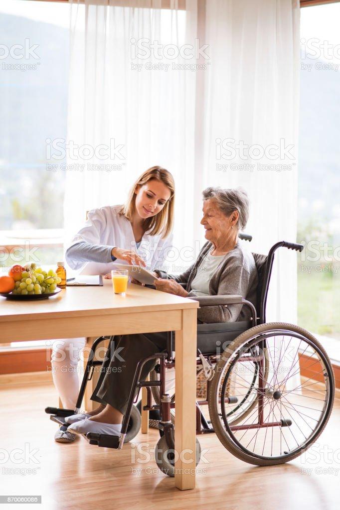 Gesundheit-Besucher und eine ältere Frau mit Tablet-PC. Lizenzfreies stock-foto