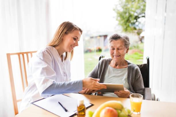 gesundheit-besucher und eine ältere frau mit tablet-pc. - heimerziehung stock-fotos und bilder
