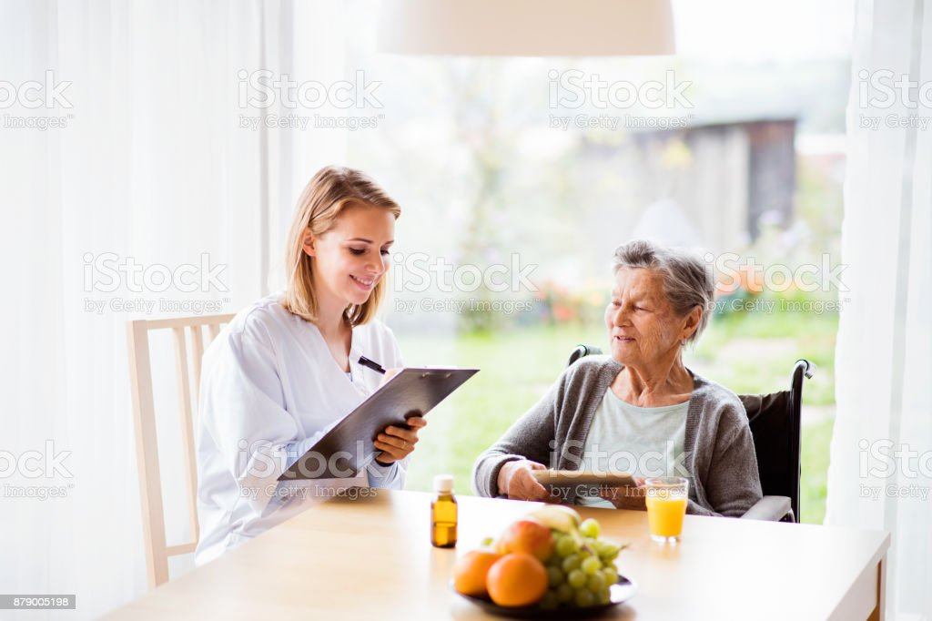 Health visitor and a senior woman with tablet. stock photo