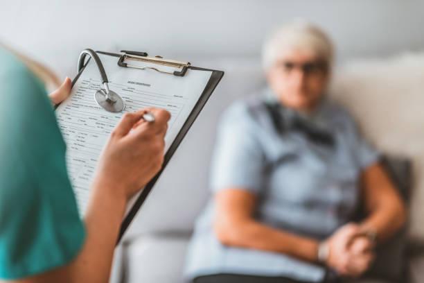 Visiteur de santé et homme aîné pendant la visite à la maison. - Photo