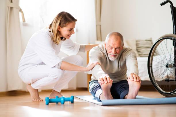 visite de santé visiteur senior homme et au cours de la maison. - sports en fauteuil roulant photos et images de collection