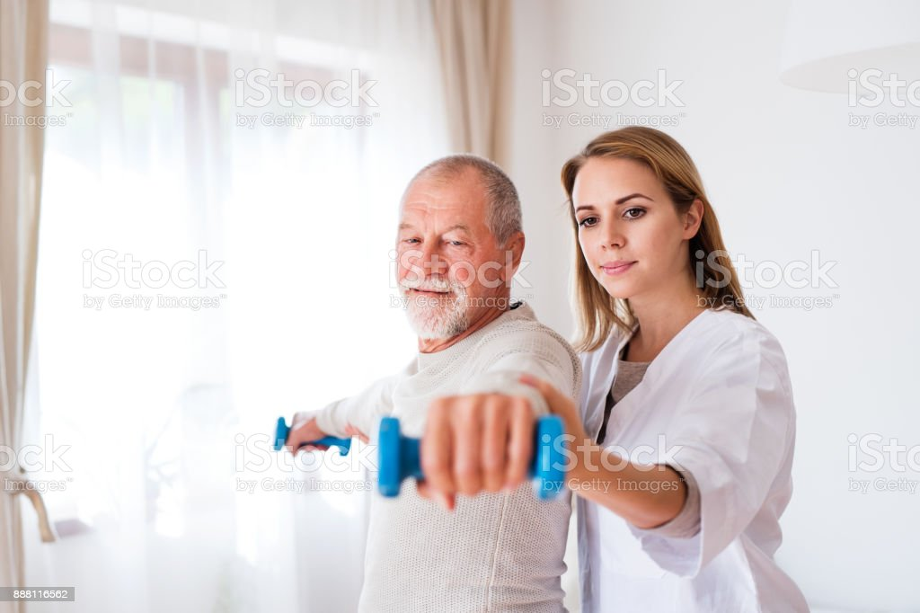 Health visitor and senior man during home visit. stock photo