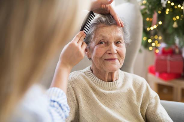 ein gesundheit besucher kämmen haare senior frau zu hause in der weihnachtszeit. - altes damenhaar stock-fotos und bilder