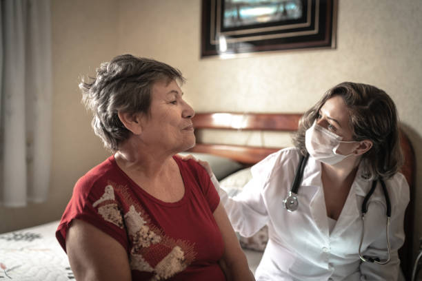 health visitor talking to a senior woman during home visit - infermiera personale medico foto e immagini stock