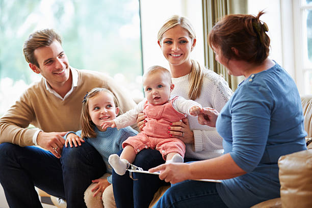 health visitor talking to family with young baby - family meeting stock photos and pictures